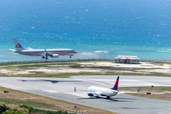 American Airlines aircraft landing while Delta waits to depart stock photography