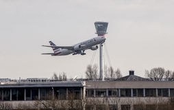 American Airlines aircraft taking off from Heathrow. American Airlines Boeing 777 taking off in front of the Air Traffic Control Tower at Heathrow London Stock Photo