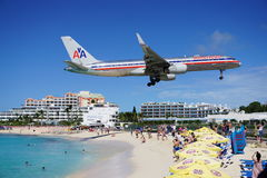 An American Airlines Boeing 757 lands over Maho Beach in St Martin. SAINT MARTIN, DUTCH ANTILLES --30 NOVEMBER 2014-- The beach at Maho Bay is one of the world's Royalty Free Stock Image