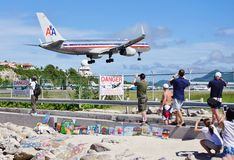 An American Airlines Boeing 757 lands over Maho Beach in St Martin. SAINT MARTIN, DUTCH ANTILLES --30 NOVEMBER 2014-- The beach at Maho Bay is one of the world's Royalty Free Stock Photography