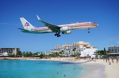 An American Airlines Boeing 757 lands over Maho Beach in St Martin. SAINT MARTIN, DUTCH ANTILLES --30 NOVEMBER 2014-- The beach at Maho Bay is one of the world's Royalty Free Stock Photos