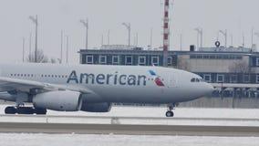 American Airlines faisant le taxi dans l'aéroport de Munich, neige banque de vidéos