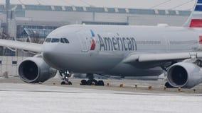 American Airlines que hace el taxi en el aeropuerto de Munich, nieve almacen de video