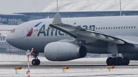 American Airlines que saca del aeropuerto de Munich, nieve almacen de metraje de vídeo