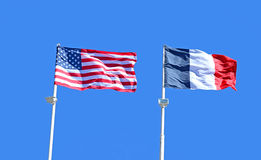 American And French Flags Against The Blue Sky Stock Images