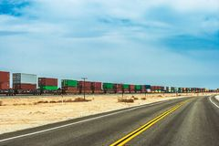 An american asphalt road with a freight train royalty free stock photography