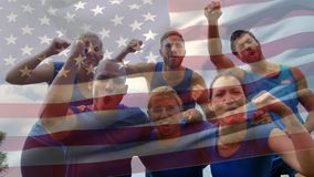 American athletes celebrating. Digital composite of diverse team of American athletes celebrating with an american flag waving in the foreground stock footage