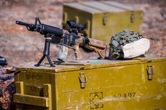 American automatic assault rifle with a sight. American assault automatic rifle with spotting scope on box of ammunition and helmet stock images