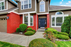 American beige house with red brick trim and dark blue front door. Stock Photos