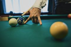 American billiard. Man playing billiard, snooker. Player preparing to shoot, hitting the cue ball. Ball number one 1 going into the hole. A simple blow from Royalty Free Stock Photos