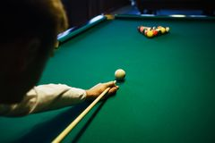 American billiard. Man playing billiard, snooker. Player preparing to shoot, hitting the cue ball. Ball number one 1 going into the hole. A simple blow from Stock Image