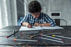 American boy. Sad Afro American boy in casual clothes is drawing using colored pencils in focus while sitting at the table at home royalty free stock image