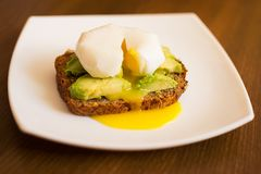 American breakfast. avocado sandwich and poached eggs on rye bread royalty free stock photos