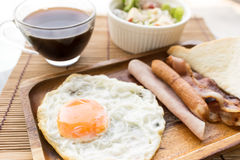 American breakfast beautiful fried egg on wood dish Royalty Free Stock Images