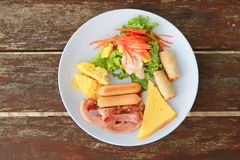 American breakfast with scrambled eggs, bacon, sausages and   fr Royalty Free Stock Photo