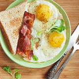 American breakfast with sunny side up eggs, bacon, toast, coffee, green salad, wood background. Top view. American breakfast with sunny side up eggs, bacon Stock Photo