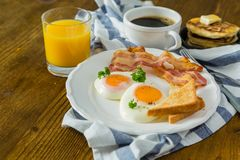 American breakfast with sunny side up eggs, bacon, toast, pancakes, coffee and juice. Wood background Stock Photos
