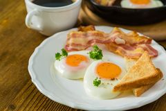 American breakfast with sunny side up eggs, bacon, toast, pancakes, coffee and juice. Wood background Royalty Free Stock Photography