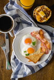 American breakfast with sunny side up eggs, bacon, toast, pancakes, coffee and juice. Wood background Stock Image