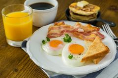 American breakfast with sunny side up eggs, bacon, toast, pancakes, coffee and juice. Wood background Royalty Free Stock Photo