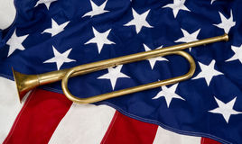 American Bugle. Brass bugle on a American flag Royalty Free Stock Images