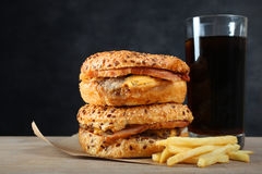 American burger, french fries. And a glass of soda on a table on a black background Stock Photos