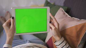 American business woman lying on the couch at home, holding a mockup green screen tablet stock footage