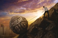 American businessman dragging text of dream big. American businessman using a chain to drag a stone with text of dream big while climbing on the cliff Royalty Free Stock Photos