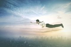 American businessman flying with a superhero pose Royalty Free Stock Images