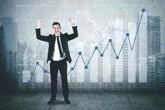 American businessman with growth graph. American businessman looks happy while celebrating his success by lifting hands and standing with growth graph stock image