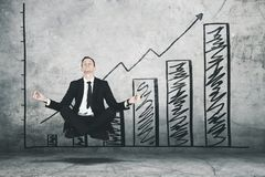 American businessman meditating with growth graph Stock Images