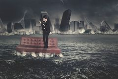 American businessman with couch in town sinking Stock Photos