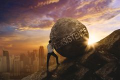 American businessman pushing persistence word. American businessman pushing a big stone with persistence word while climbing on the cliff. Shot at sunset time Royalty Free Stock Photos