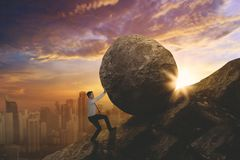 American businessman struggling to push a stone. While climbing on the cliff. Shot at sunset royalty free stock photos