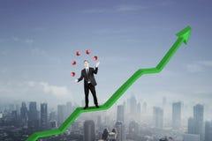 American businessman with symbols and arrow. American businessman juggling with symbols while standing on an upward arrow Royalty Free Stock Photo