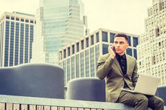 Young American Businessman traveling, working in New York. American Businessman traveling, working in New York, wearing green suit, siting at street park in Stock Image