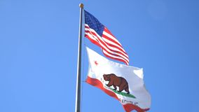The American and California flag fluttering stock video footage