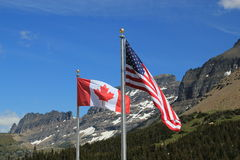 American and Canadian flags. Showing the full stars and stripes and maple leaf respectively, on silver flagpoles blowing in the wind against a backdrop of snow Royalty Free Stock Photos
