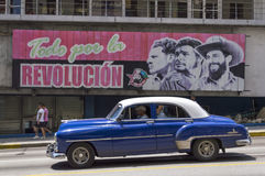 American cars under a cuban propaganda billboard. A blue old american car running in Havana, Cuba under a governative propaganda billboard royalty free stock photography