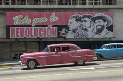 American cars under a cuban propaganda billboard. A couple of old american cars from the fifties, running in Havana, Cuba under a governative propaganda royalty free stock photography