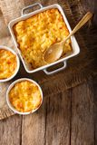 American casserole macaroni and cheese in baking dish close up. American casserole macaroni and cheese in baking dish close up on the table. Vertical top view Royalty Free Stock Images