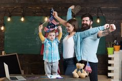 American cheerful family with son and usa flags. Kid with parents in classroom with usa flags, chalkboard on background. Parents teaching son american Royalty Free Stock Photo