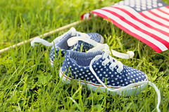 American children's sneakers and United States of America flag. American children's sneakers and United States of America flag on green grass background. Kid' Stock Image