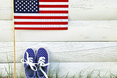 American childrens sneakers and United States of America flag. American childrens sneakers and United States of America flag on white wooden background. Kid's Stock Photos