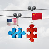 American And Chinese Cooperation. Success as two pieces of a jigsaw puzzle from the United States and China coming together to unite as a global teamwork Royalty Free Stock Images