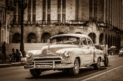 American classic car drives on the main street with street life view in Havana Cuba - Retro Ser. Ie SEPIA Cuba Reportage Royalty Free Stock Photo
