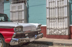 American classic car in front of a colonial house in Trinidad, Cuba. A detail of a red and white classic american car, in front of a typical colonial house Royalty Free Stock Photo