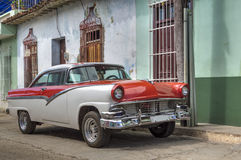 American classic car in front of a colonial house in Trinidad, Cuba. A red and white classic american car, in front of a typical colonial house, Trinidad, Cuba royalty free stock photo