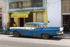 American classic car in front of a local Cafè, Havana, Cuba. A blue and white classic american car, in front of a cuban cafeteria in Havana royalty free stock images