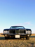 American Classic Car - Open Green. An american classic convertible from 1970s parked in a field under a blue sky Stock Photos